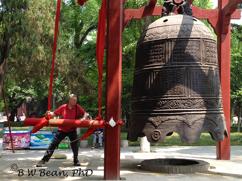Your Author - striking the bell at the Small Goose Pagoda in Xian. bwb-images